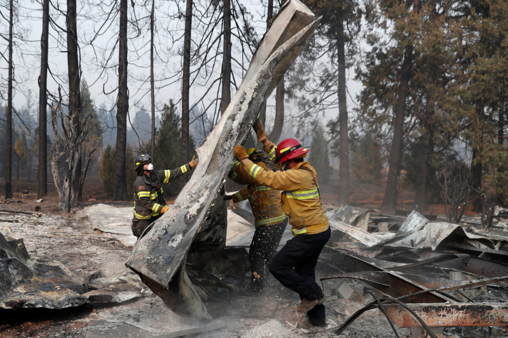 Firefighters move debris while recovering human remains from a trailer home destroyed by the Camp Fire in Paradise, Califo...