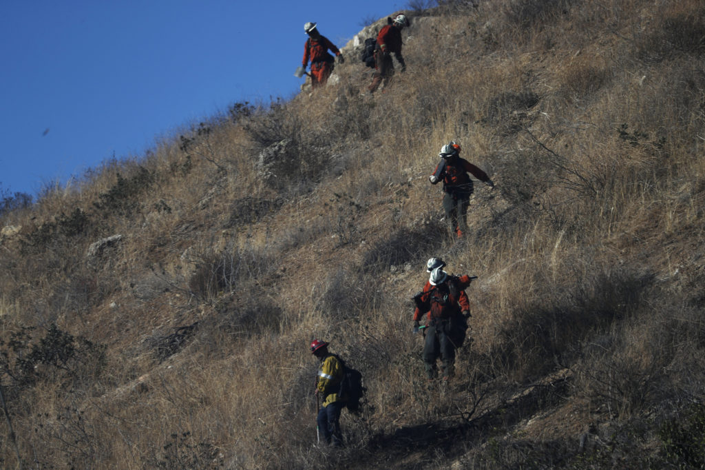 Firefighters and prison crews walk among chaparral and battle the Woolsey fire in West Hills, Southern California, U.S. November 11, 2018. Photo by REUTERS/Mario Anzuoni