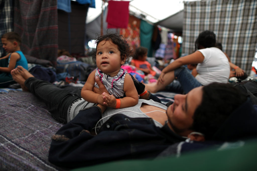 Cesar Elvir 20 from Honduras and his one-year-old cousin Ahslyn part of a caravan of thousands of migrants from Central America trying to reach the United States rest in temporary shelter in Tijuana Mexico