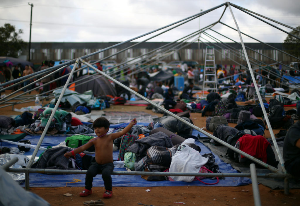 A migrant boy, part of a caravan of thousands from Central America trying to reach the United States, rests in a temporary shelter in Tijuana, Mexico, November 24, 2018. Photo by Hannah McKay/Reuters