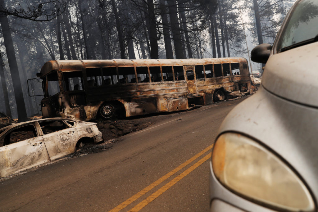 An abandoned and burned school bus is seen on Skyway during the Camp Fire in Paradise, California, U.S. November 9, 2018. Photo by REUTERS/Stephen Lam