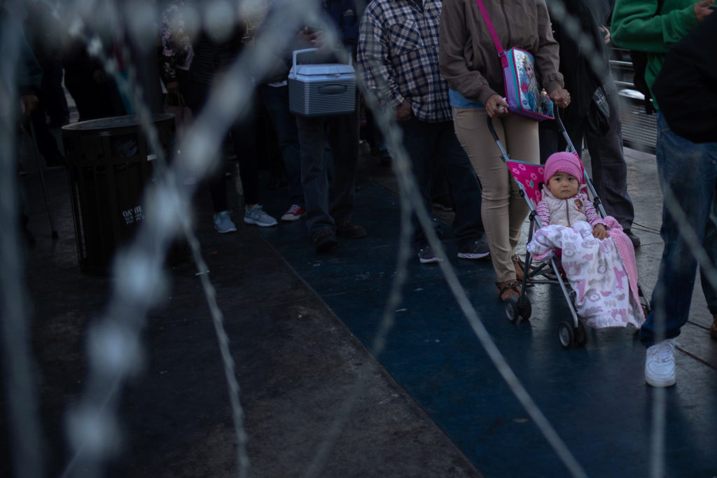Concertina wire is seen as people await in line at the San Ysidro Port of Entry after the land border crossing was temporarily closed to foot and vehicle traffic from Tijuana, Mexico November 19, 2018. REUTERS/Adrees Latif