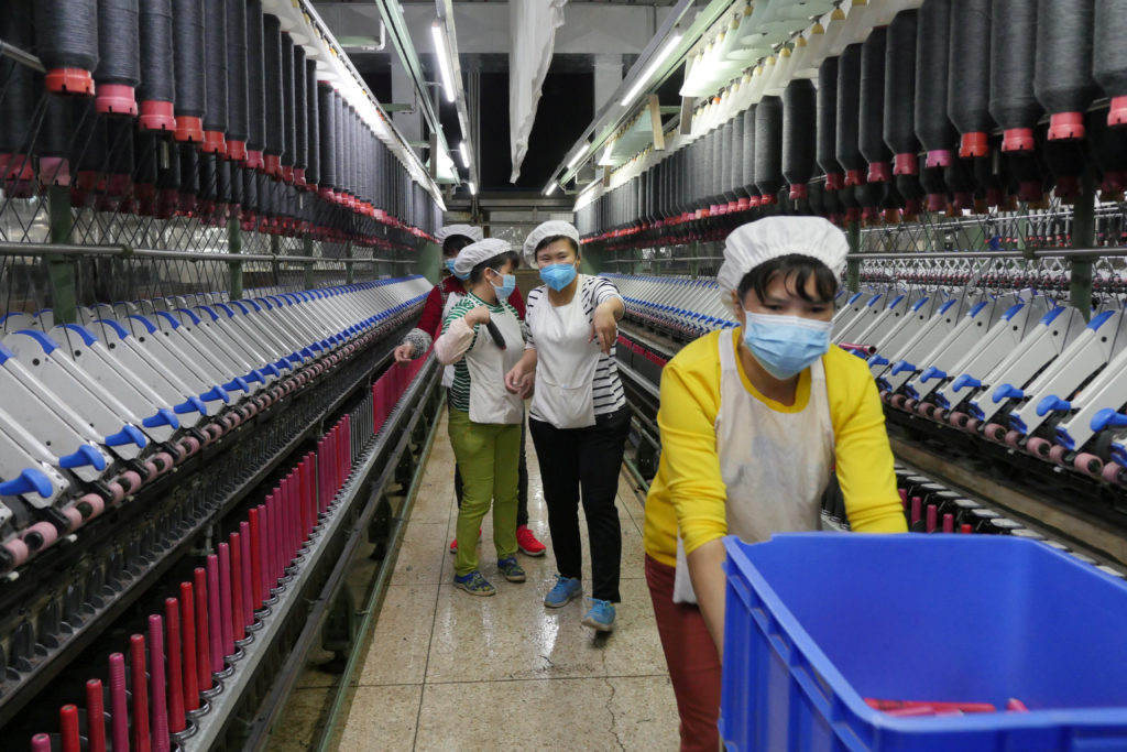 A worker jokes and beckons at her colleague as she rolls away carts of unused tools between rows of spinning machine at a factory owned by Hong Kong's Novetex Textiles Limited in Zhuhai City, China, in 2016. Photo by Venus Wu/Reuters