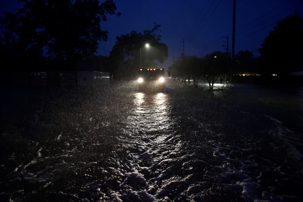 A civilian owned military vehicle drives through floodwaters performing search and rescue after Hurricane Harvey inundated...