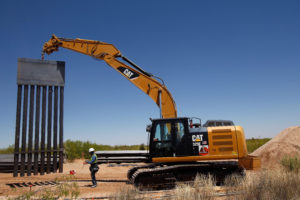A construction worker stands by heavy machinery carrying a panel of new bollard wall in Santa Teresa, New Mexico, as seen from the Mexican side of the border in San Jeronimo, on the outskirts of Ciudad Juarez, Mexico. Photo by Jose Luis Gonzalez/Reuters