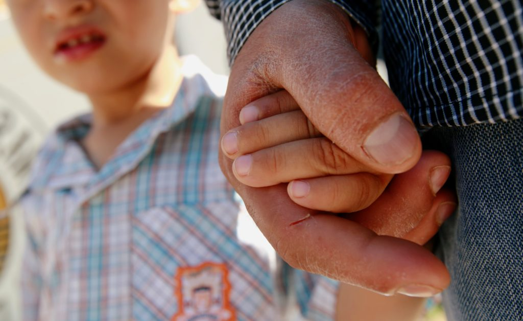 A Salvadoran migrant father holds the hand of his 3-year-old son in Ciudad Juarez, Mexico, in June 2018. Photo by Jose Lui...