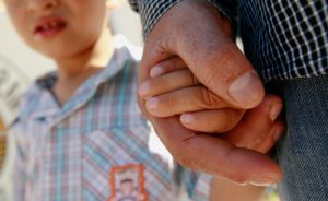 A Salvadoran migrant father holds the hand of his 3-year-old son in Ciudad Juarez, Mexico, in June 2018. Photo by Jose Luis Gonzalez/Reuters