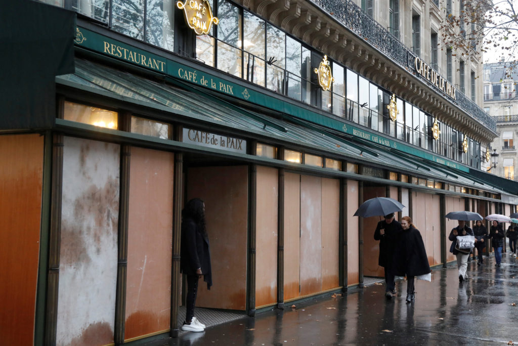 """Pedestrians walk past wood panels protecting the """"Cafe de la Paix"""" on the eve of a """"yellow vests"""" protest in Paris, France..."""