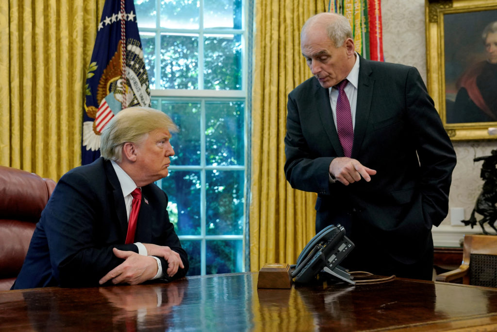 President Donald Trump speaks to White House Chief of Staff John Kelly after an event with reporters in the Oval Office at...