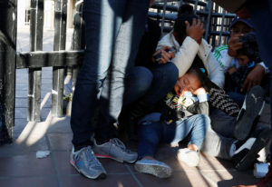 The daughter of Maria Meza, a 40-year-old migrant woman from Honduras, part of a caravan of thousands from Central America trying to reach the United States, sleeps as she waits with her mother sitting at the Otay Mesa port of entry in San Diego to be processed as asylum seeker, as seen from Tijuana, Mexico. Photo by Mohammed Salem/Reuters