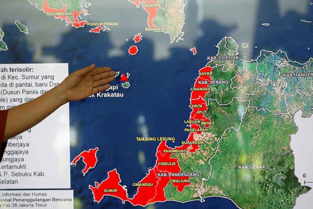 Sutopo Purwo Nugroho, a spokesman of Indonesia's Mitigation and Disaster Agency (BNPB), spots on a map of area affected by a tsunami hit Sunda straitduring during a conference at the BNPB headquarters in Jakarta, Indonesia. Photo by Willy Kurniawan/Reuters