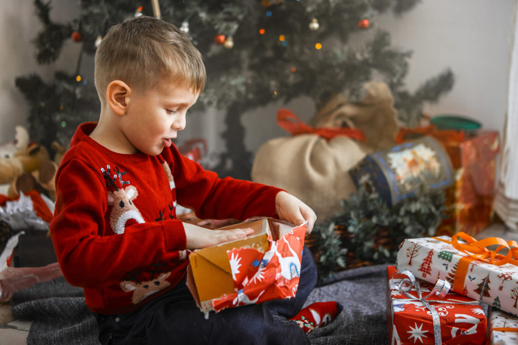 A young boy unwraps a holiday present. But what will happen to the wrapping paper? Image by olly via Adobe Stock Images