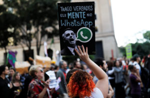 "A woman holds a sign with an image of presidential candidate Jair Bolsonaro that reads ""He lies in WhatsApp,"" during a protest against Bolsonaro in Sao Paulo, Brazil, October 20, 2018. Photo by REUTERS/Nacho Doce"