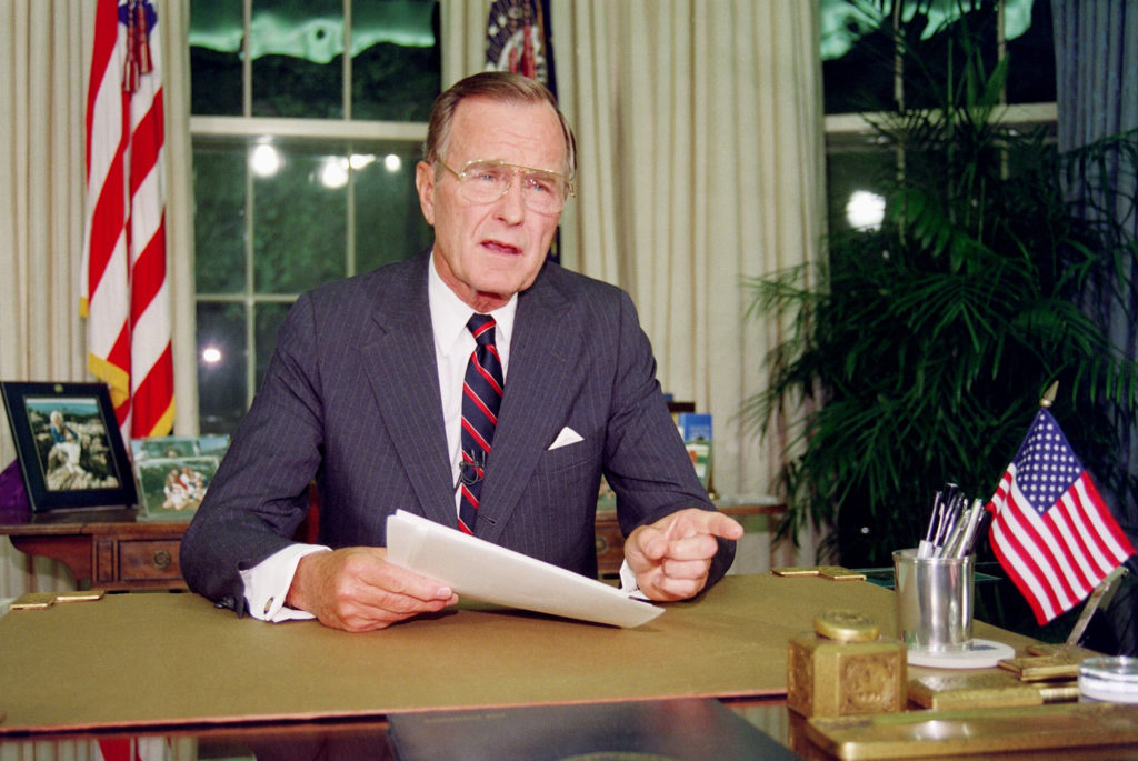 President George H.W. Bush poses for photographers after his address to the nation, September 1991, in the Oval Office of the White House. Photo by Luke Frazza/AFP/Getty Images