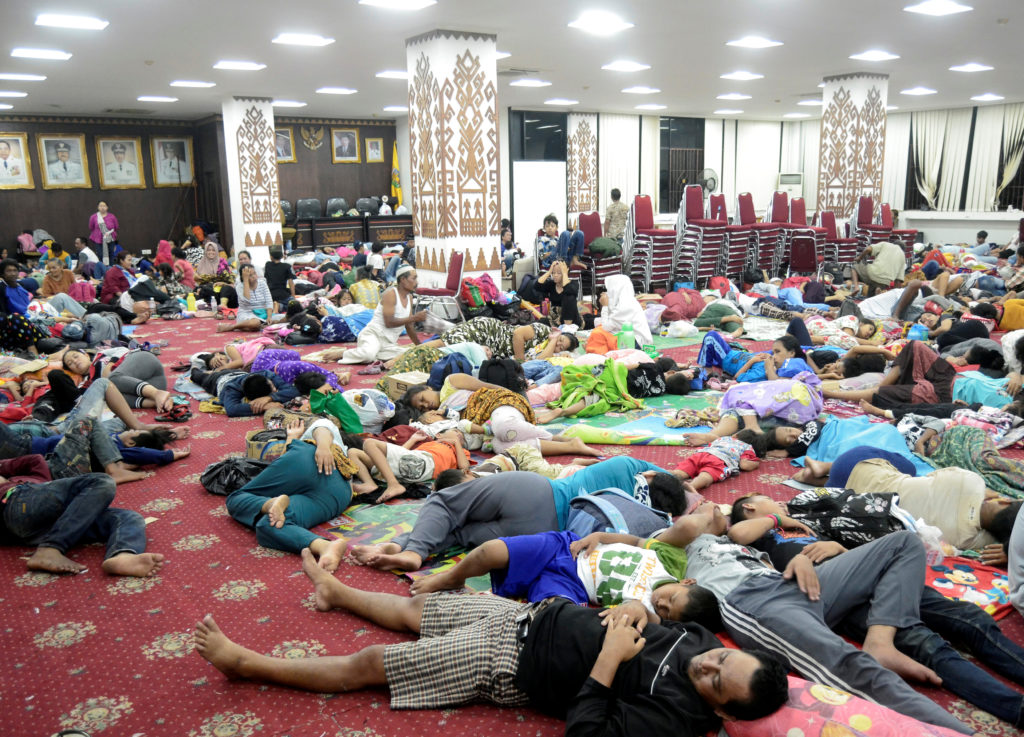 Residents, who lived at coast of Bandar Lampung, rest at government building after they evacuated following a tsunami hit Sunda strait in Lampung, Indonesia. Photo by Antara Foto/Ardiansyah via Reuters