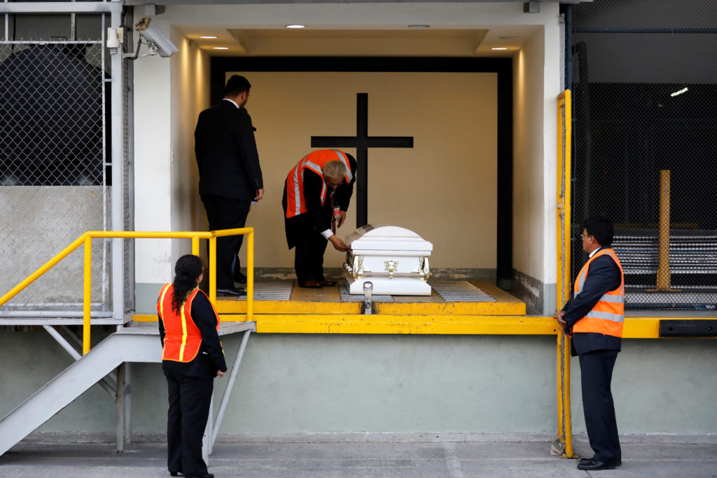 Staff of a funeral home receive the coffin containing the body of Jakelin Caal before her funeral, at La Aurora Internatio...