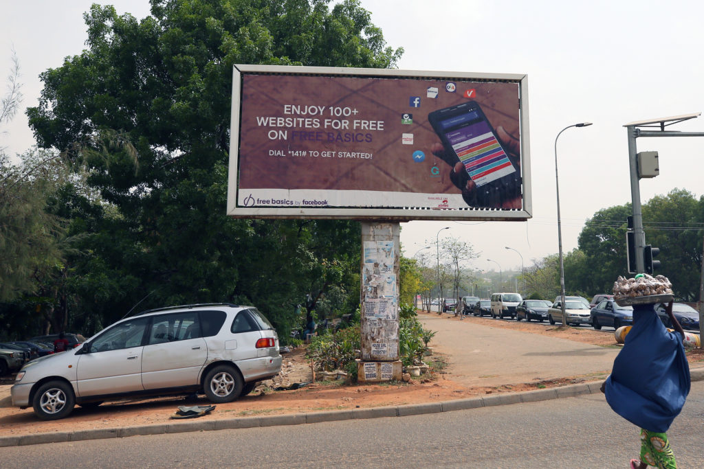 A woman walks past an advertising billboard for Free Basics, a service from Facebook, along a street in Abuja, Nigeria April 4, 2018. Photo by REUTERS/Afolabi Sotunde