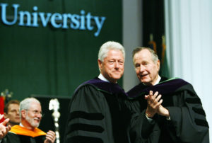 Former U.S. Presidents Bill Clinton (L) and George Bush stand on the podium at the Tulane University commencement in New Orleans May 13, 2006. Photo by Alex Brandon/Pool via Reuters