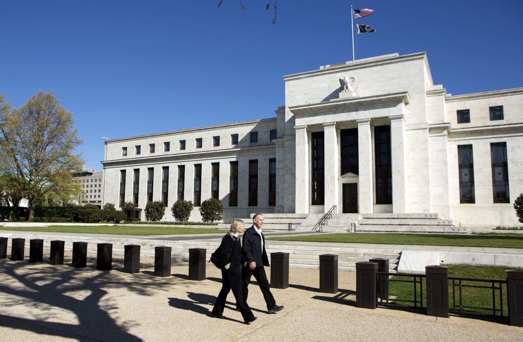 Pedestrians walk past the Federal Reserve Building in Washington, D…
