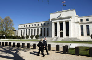 Pedestrians walk past the Federal Reserve Building in Washington, D.C. Photo by Joshua Roberts/Reuters