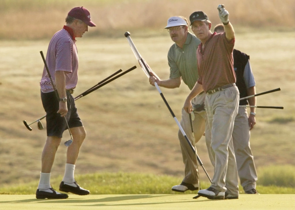 U.S. President George W. Bush (R) and his father, former President George Bush (L), play the tenth hole during a round of golf at the Cape Arundel Golf Club in Kennebunkport, Maine, August 3, 2002. The elder Bush has recently undergone topical treatment for sun induced keratoses, which are focal areas of damage in the top layers of skin caused by sun exposure over the years. At center is club pro Ken Raynor. REUTERS/Win McNamee  WM/HB - RP3DRIAZLHAA
