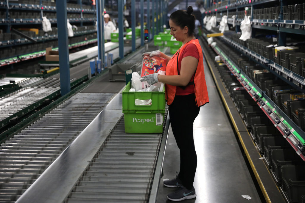 "A grocery ""picker"" works in a Peapod grocery distribution warehouse facility in Jersey City. The warehouse sector saw a significant uptick in hiring in November, according to the Bureau of Labor Statistics. Photo by Mike Segar/Reuters"