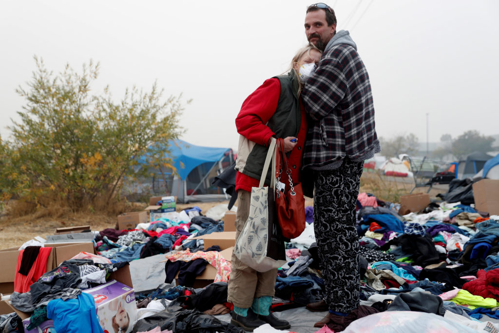 Travis Lee Hogan, of Paradise, comforts his mother, Bridgett Hogan, while they stay at a makeshift evacuation center for people displaced by the Camp Fire in Chico, California. Photo by Terray Sylvester/Reuters