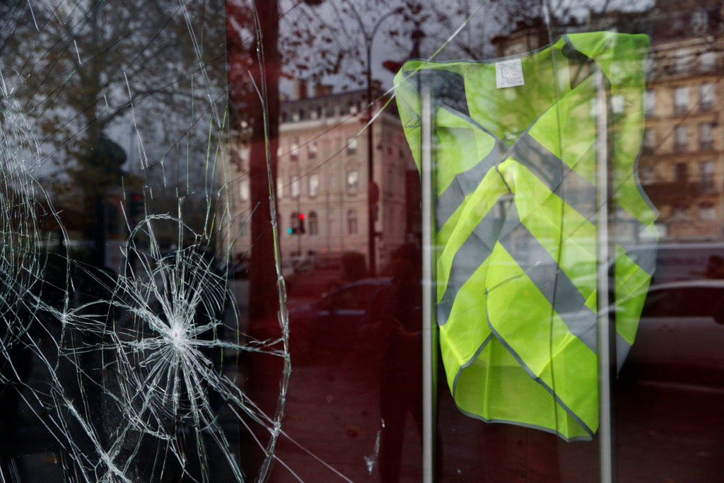 A yellow vest hangs inside a vandalized store front the morning after clashes with protesters wearing yellow vests, a symbol of a French drivers' protest against higher diesel fuel taxes, in Paris. Photo by Stephane Mahe/Reuters