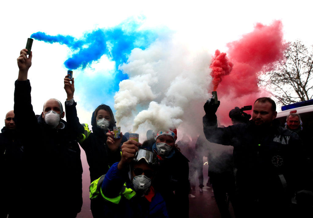 French ambulance drivers hold blue, white, red smoke bombs during a demonstration at the Place de la Concorde in Paris. Photo by Gonzalo Fuentes/Reuters