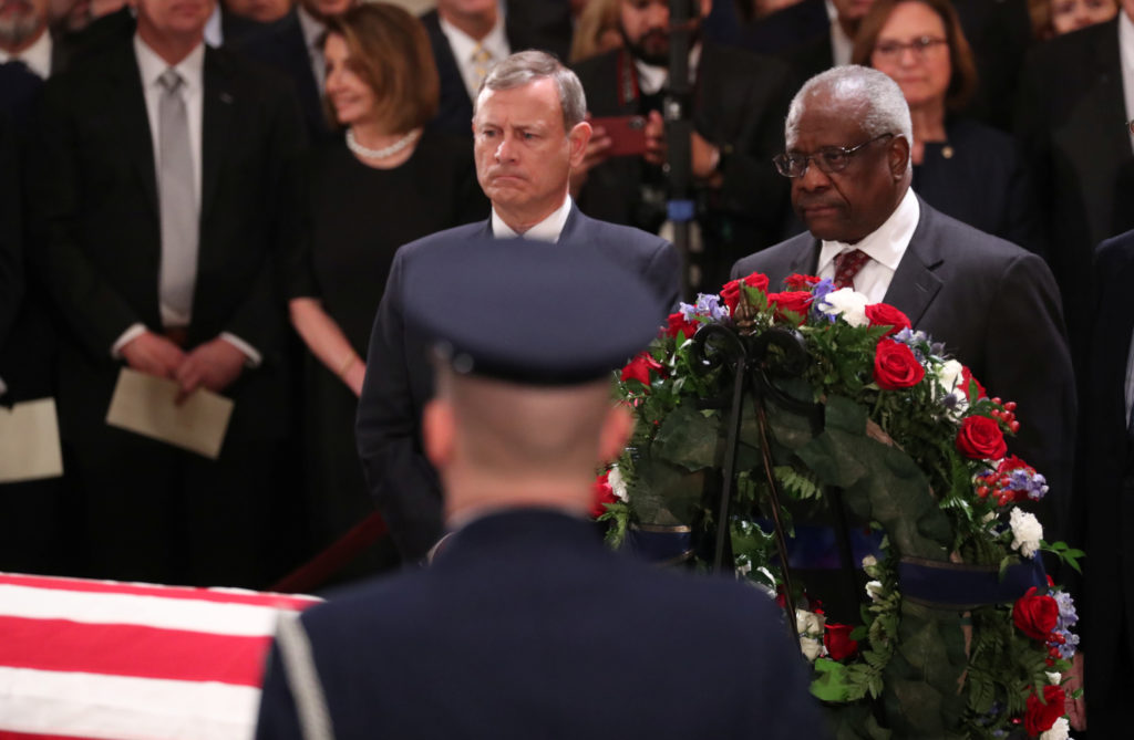 Supreme Court Chief Justice John Roberts and Associate Justice Clarence Thomas, who was nominated to the Supreme Court by former President George H.W. Bush, stand before the late president's casket together inside the U.S. Capitol Rotunda on Capitol Hill in Washington, D.C. Photo by Jonathan Ernst/Reuters