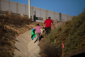 Migrants from Honduras, part of a caravan of thousands from Central America trying to reach the United States, climb a hill after crawling through a hole under a border wall to cross illegally from Mexico to the U.S, photographed through the border wall from Tijuana, Mexico. Photo by Alkis Konstantinidis/Reuters