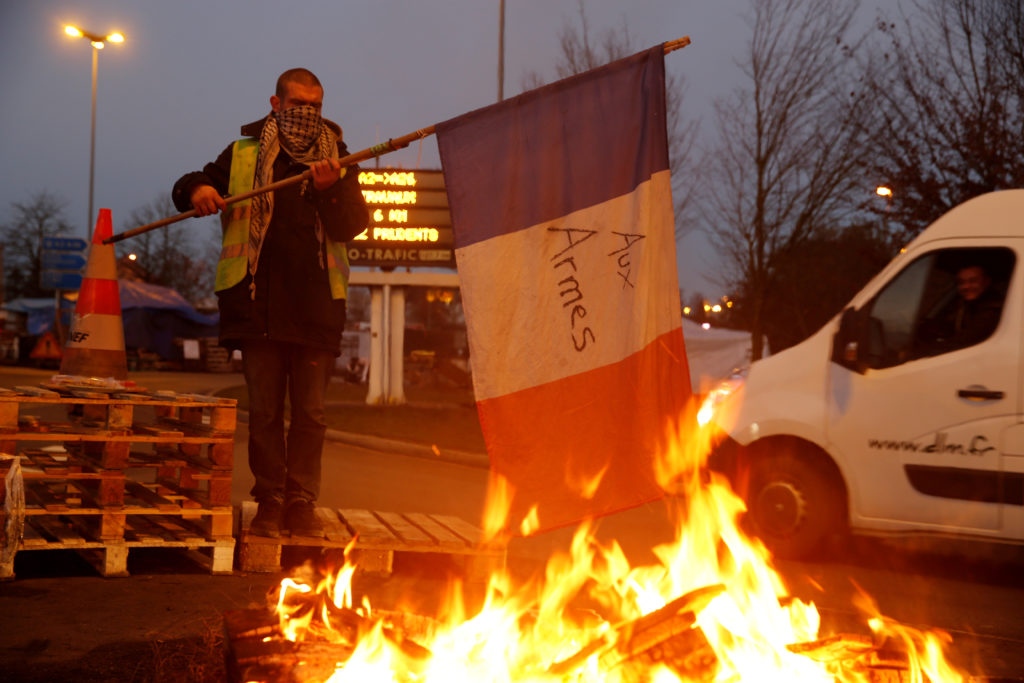 A protester wearing a yellow vest, the symbol of a French drivers' protest against higher diesel fuel prices, holds a flag...