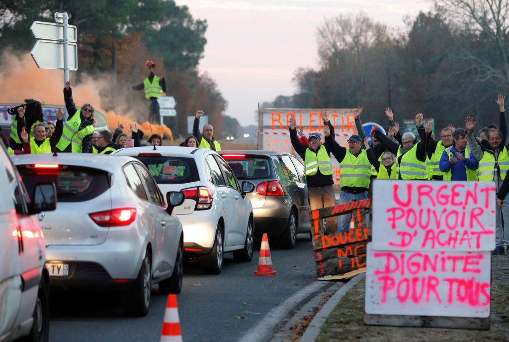 "Protesters wearing yellow vests, the symbol of a French drivers' protest against higher diesel fuel prices, occupy a roundabout in Cissac-Medoc, France. The slogan reads ""Urgent, purchase power, dignity for all."" Photo by Regis Duvignau/Reuters"
