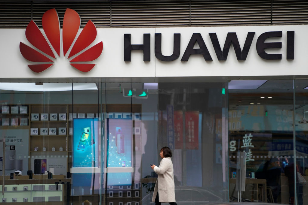 A woman walks by a Huawei logo at a shopping mall in Shanghai, China. Photo by Aly Song/Reuters