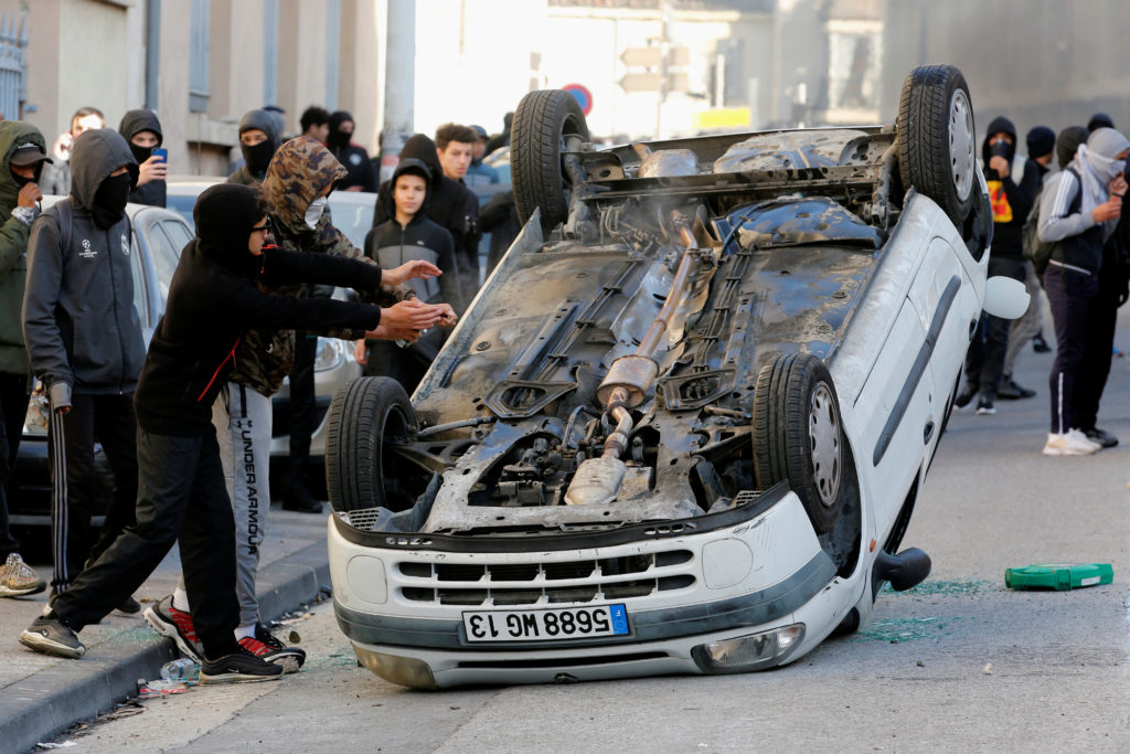 A vandalized car is seen in the street as youths and high-school students clash with police during a demonstration against the French government's reform plan in Marseille, France, December 6, 2018. Photo by Jean-Paul Pelissier/Reuters