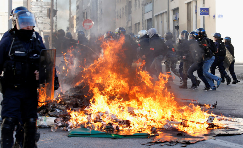 Trash bins burn as youths and high-school students clash with police at a demonstration against the French government's reform plan in Marseille, France, December 6, 2018. Photo by Jean-Paul Pelissier/Reuters