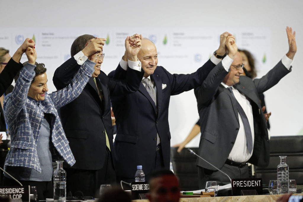 National and international leaders at react during the final plenary session at the World Climate Change Conference 2015 near Paris on December 12, 2015.  The agreement garnered widespread support from nations in part because the carbon reduction goals were voluntary. Photo by Stephane Mahe/Reuters