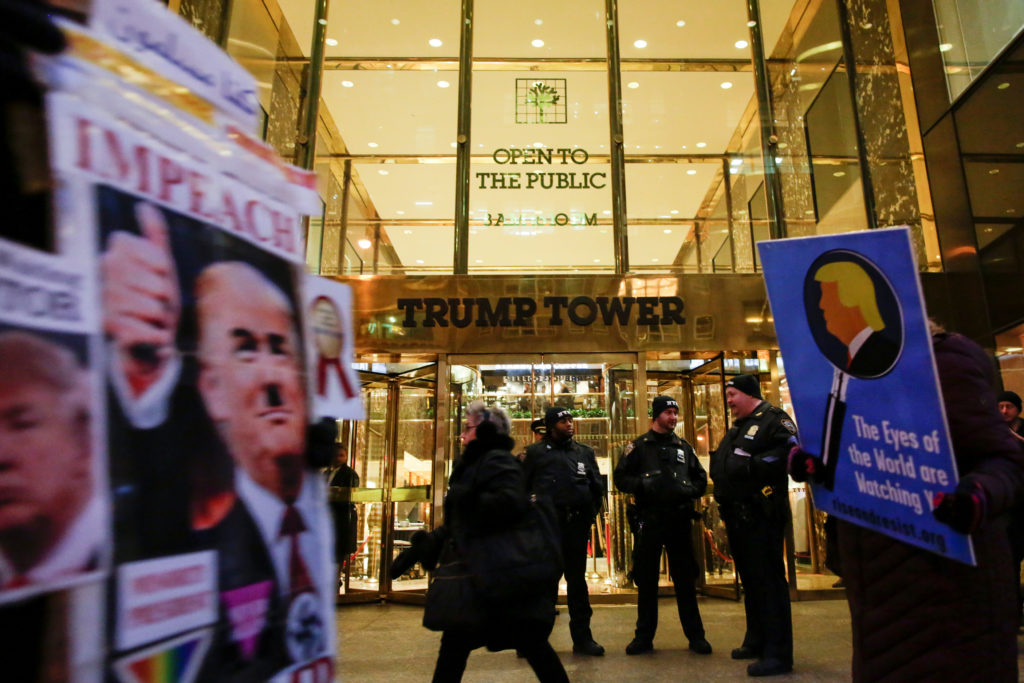 New York Police Department (NYPD) officers stand guard outside Trump Tower as people participate in a protest, in New York...