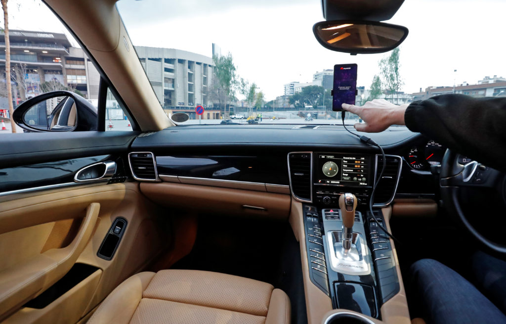 An engineer points to a Huawei Mate 10 Pro mobile used to control a driverless car during the Mobile World Congress in Barcelona, Spain. Photo by Yves Herman/Reuters