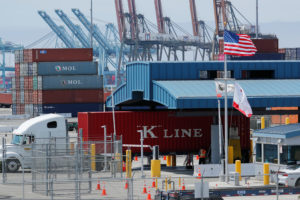 Trucks offload containers from ship at the port of Los Angeles. Photo by Mike Blake/Reuters