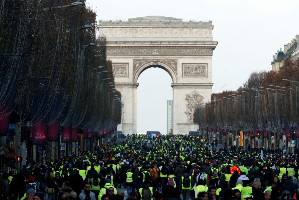 Protesters wearing yellow vests walk on the Champs Elysees Avenue with the Arc de Triomphe in the background during a national day of protest by the