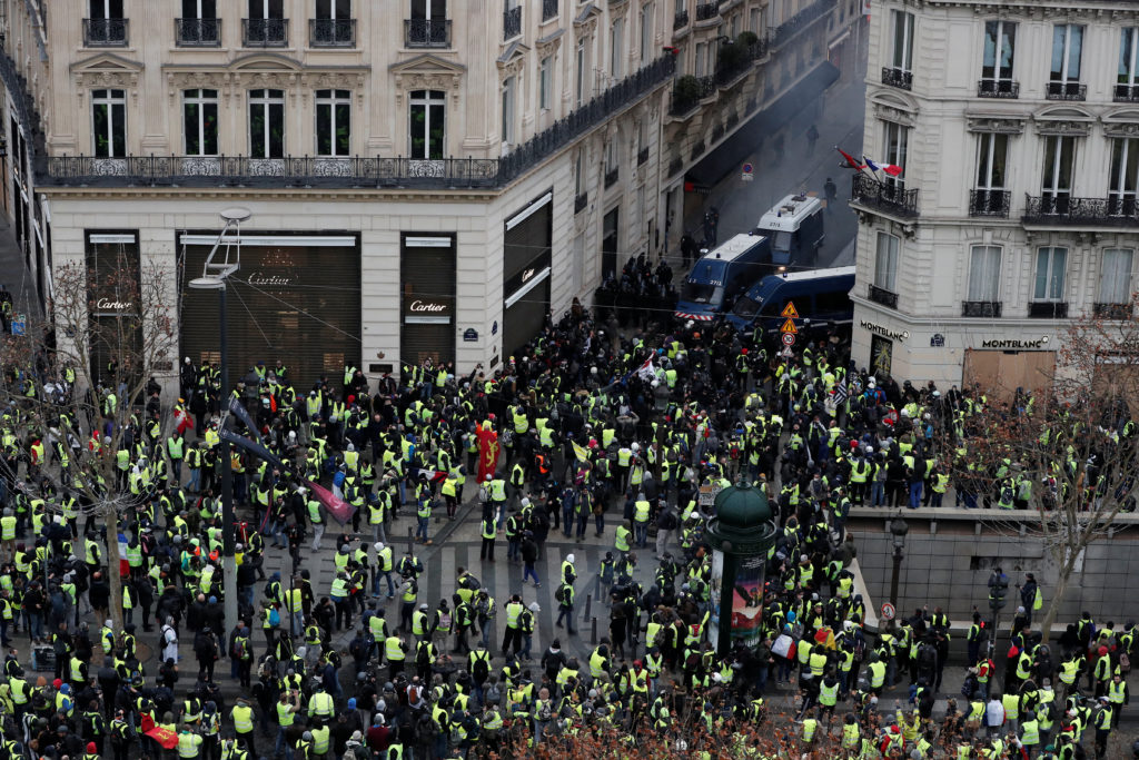 """Protesters wearing yellow vests face off with French Gendarmes on the Champs-Elysees Avenue during a demonstration by the """"yellow vests"""" movement in Paris, France, December 8, 2018. Photo by Benoit Tessier/Reuter"""