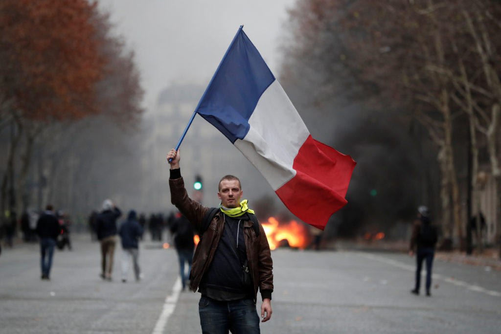 """A protester waves a French flag during clashes with police at a demonstration by the """"yellow vests"""" movement in Paris, France, December 8, 2018. Photo by Benoit Tessier/Reuters"""