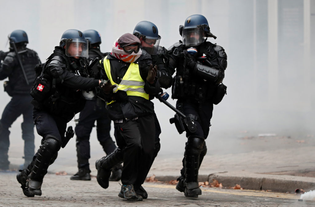 French gendarmes apprehend a protester during clashes at a demonstration by the
