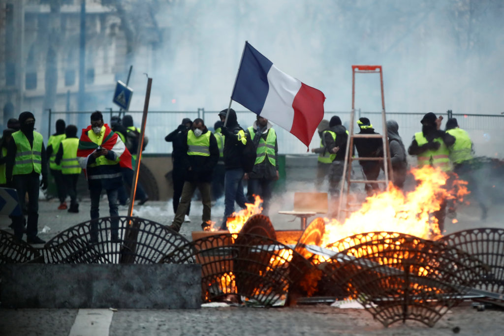 """Protesters wearing yellow vests stand behind a barricade as they face off with police during clashes as part of a national day of protest by the """"yellow vests"""" movement in Paris, France, December 8, 2018. Photo by Christian Hartmann/Reuters"""