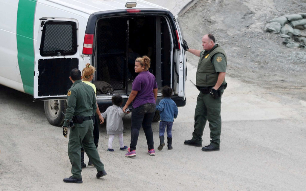 U.S. Customs and Border Protection (CBP) officials detain a migrant woman and children, part of a caravan of thousands from Central America trying to reach the United States, after they crossed illegally with other migrants from Mexico to the U.S, at International Friendship Park, in San Diego, U.S., December 9, 2018. Picture taken from Tijuana, Mexico. Photo By Mohammed Salem/Reuters