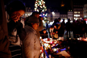 People cry as they light candles in tribute to the victims of the deadly shooting in Strasbourg, France on December 13, 2018. Photo by Christian Hartmann/Reuters
