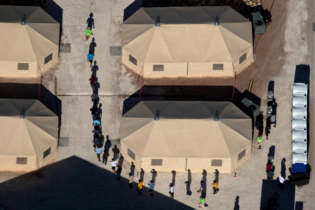 Immigrant children are led by staff in single file between tents at a detention facility next to the Mexican border in Tornillo, Texas, in June 2018. Photo By Mike Blake/Reuters