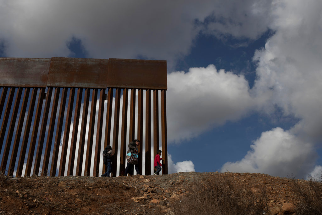 Migrants from Guatemala seeking asylum, walk to the edge of the border wall before illegally crossing into the United States from the outskirts of Tijuana into San Diego County Dec. 1, 2018. Photo Adrees Latif