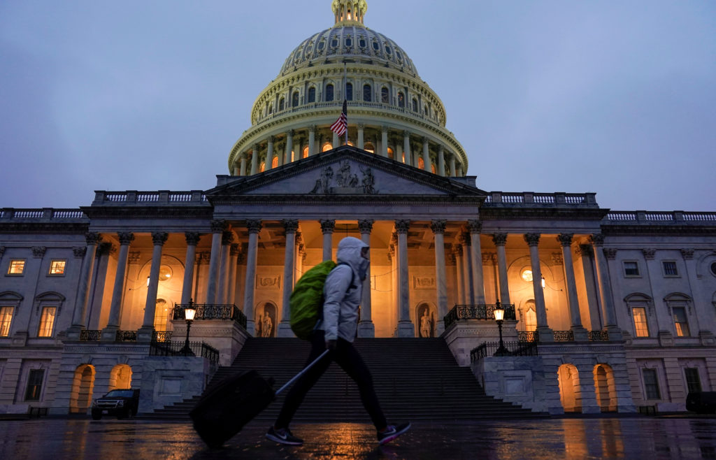 A pedestrian walk past the U.S. Capitol ahead of a possible partial government shut down in Washington, U.S., December 20,...